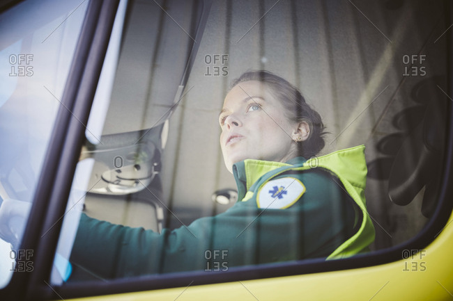 Thoughtful mid adult paramedic sitting in ambulance