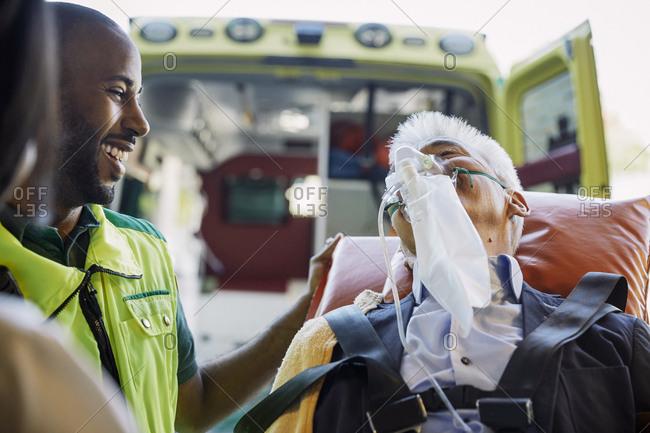 Smiling male paramedic encouraging businessman against ambulance