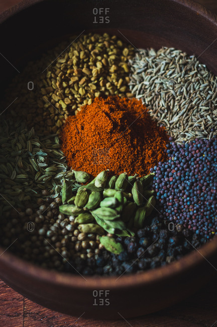 Close up of various spices in a wooden bowl for making curry powder