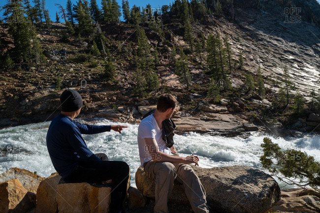 Two men sitting on rocks overlooking raging river in the wilderness