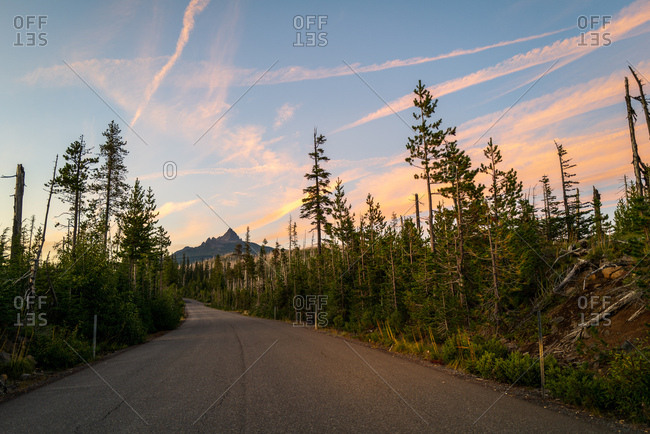 Sunset sky over mountain and tree lined road