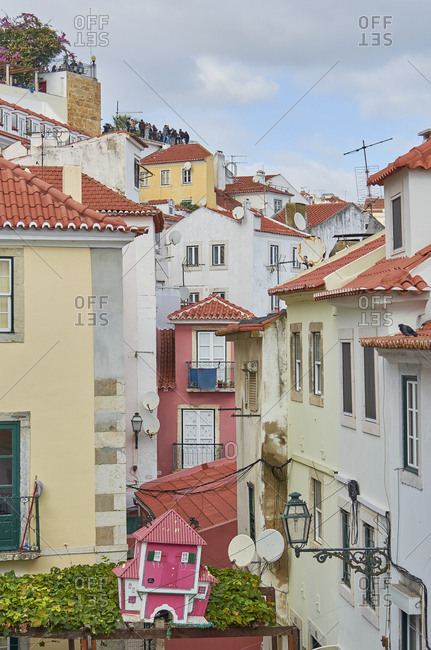 Lisbon, Portugal - November 3, 2018: Buildings in Alfama, Lisbon with people on rooftop