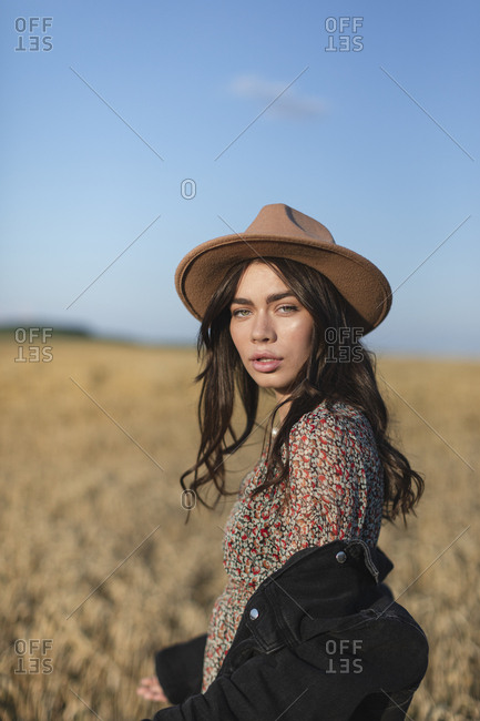 Portrait of a beautiful young woman in stylish hat standing in a field