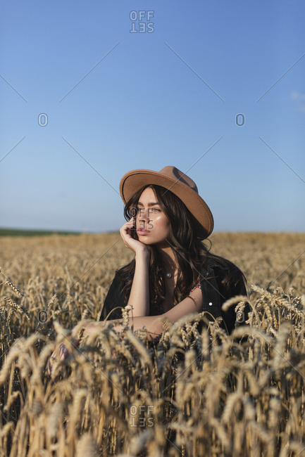 Portrait of a beautiful young woman in stylish hat sitting in a field