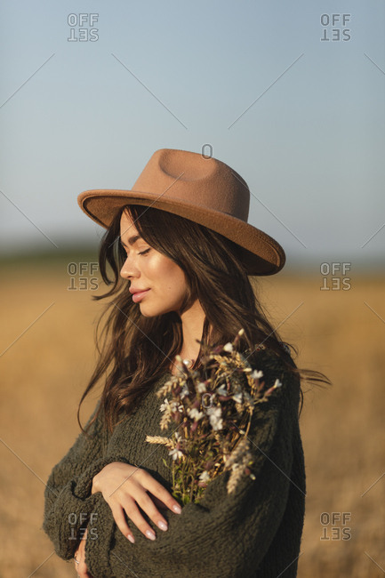 Portrait of a beautiful young woman in stylish hat holding wheat