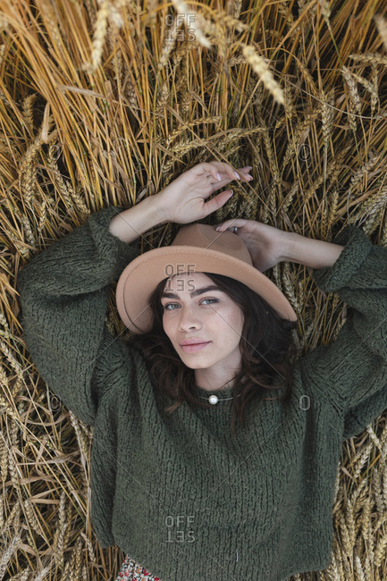 Overhead view of a young woman in stylish hat lying in a wheat field