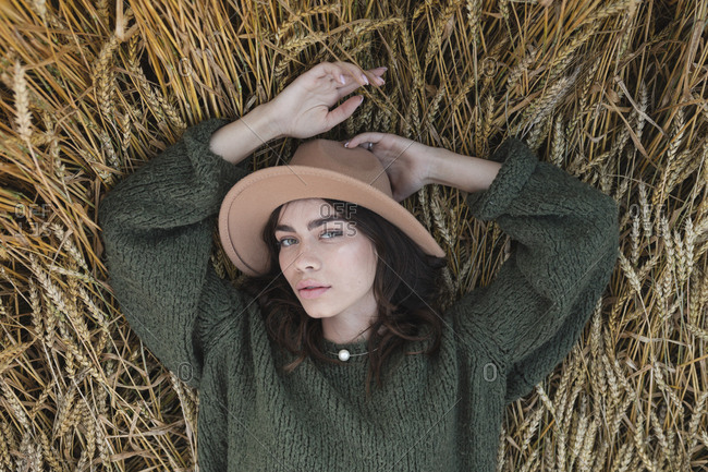 High angle view of a young woman in stylish hat lying in a wheat field