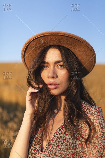 Portrait of a beautiful young woman in stylish hat standing in a field at sunset