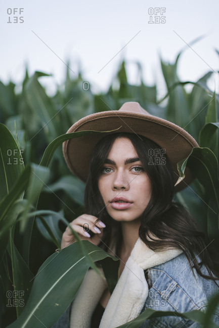 Portrait of a beautiful young woman in stylish hat standing in a corn field