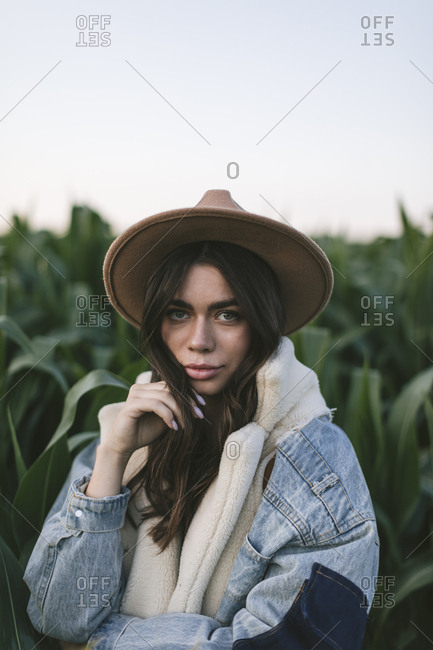 Portrait of a beautiful young woman in stylish hat and jean jacket standing in a corn field