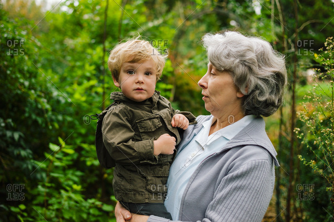 Grandmother hugs her grandson in a flowered garden with trees hand in hand