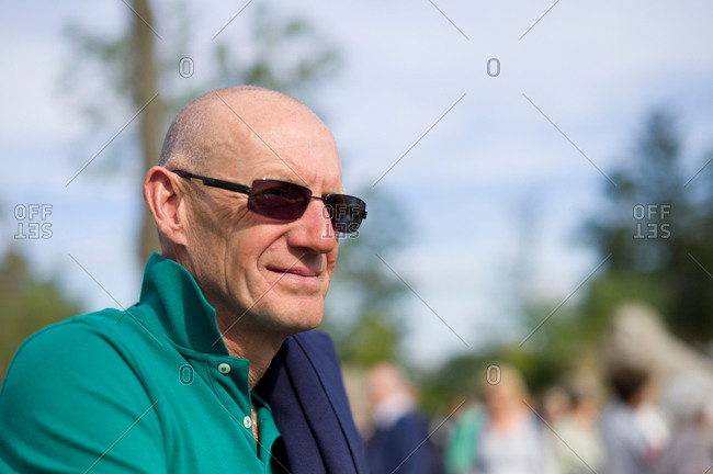 Mature man with sunglasses looks away in a park, smiling