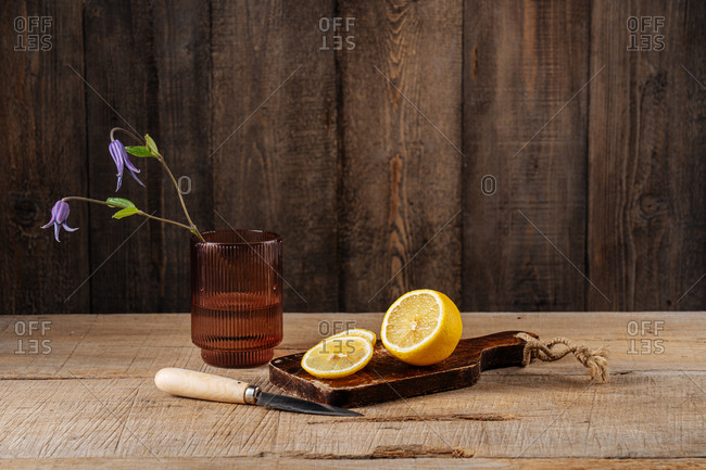 Lemon sliced on cutting board by glass with purple flowers