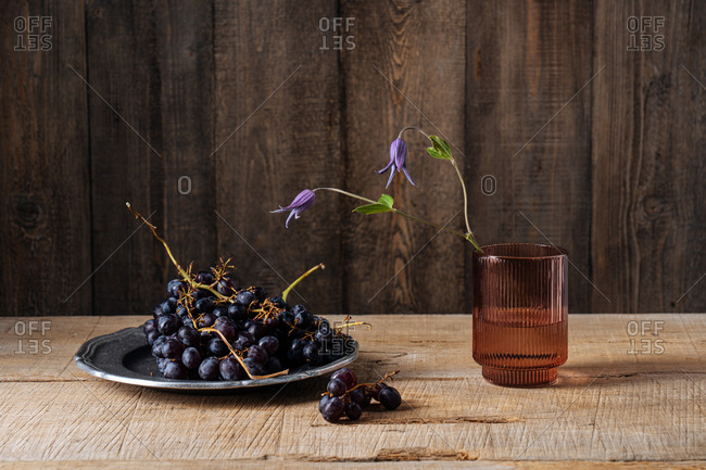 Purple flowers blossoming in a brown glass beside grapes