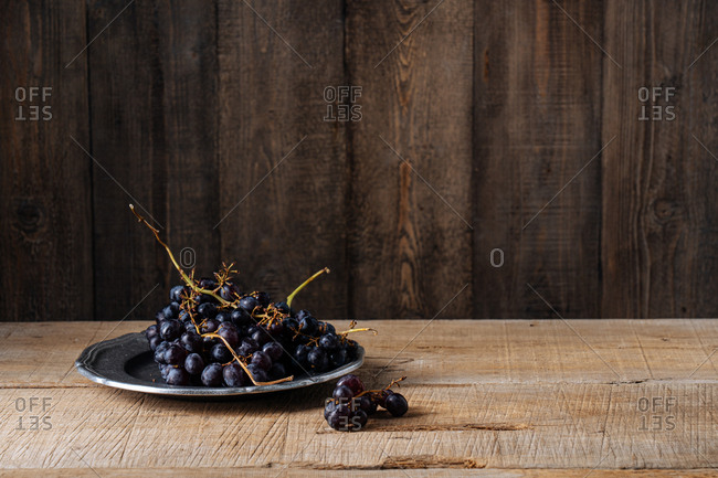 Bunch of grapes on a silver plate on wooden surface