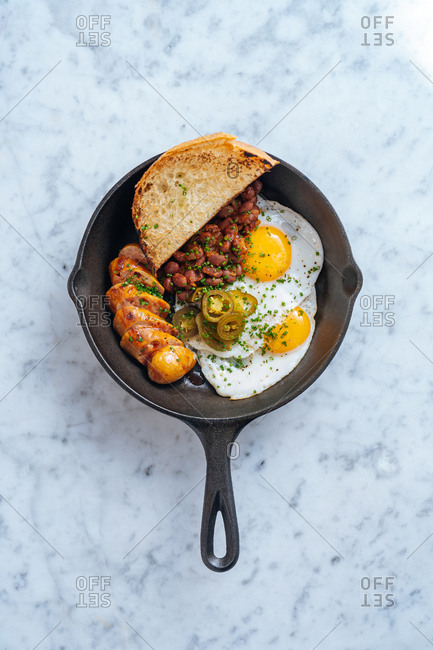 Overhead view of a breakfast skillet on white marble background