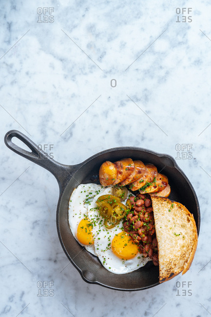 Top view of a breakfast skillet on white marble background