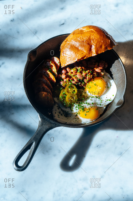 A breakfast skillet on white marble background