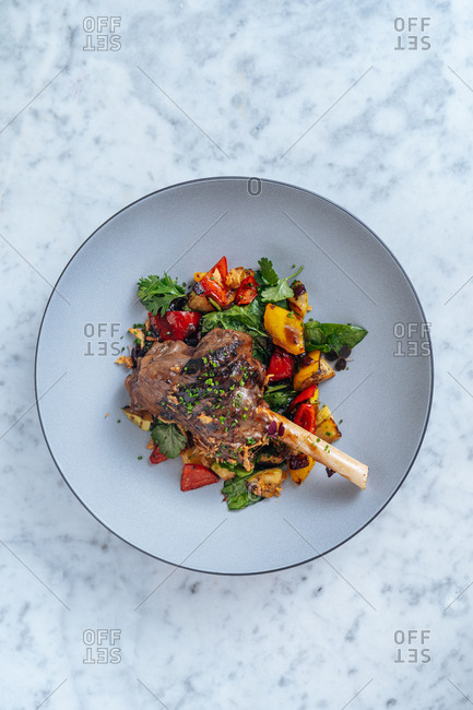 Overhead view of a colorful gourmet lamb dish on a marble surface