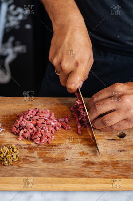 Chef dicing red meat on wooden cutting board