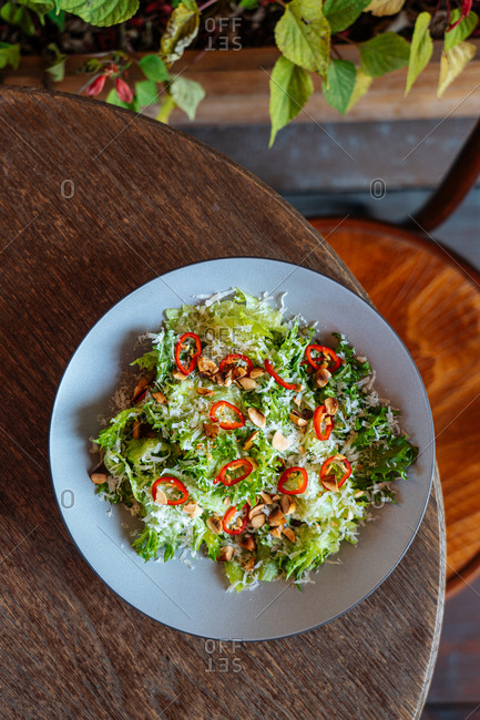 Overhead view of a salad with red pepper and nuts on a wooden table