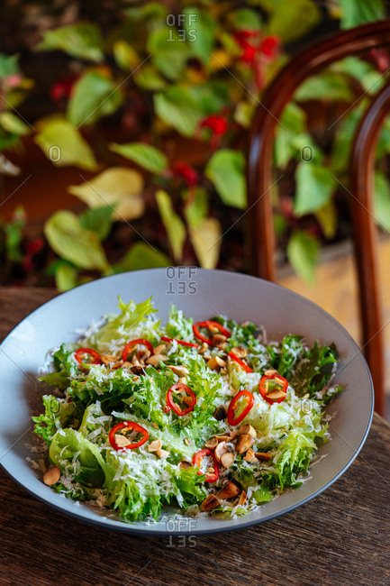 A salad with red pepper and nuts on a wooden table