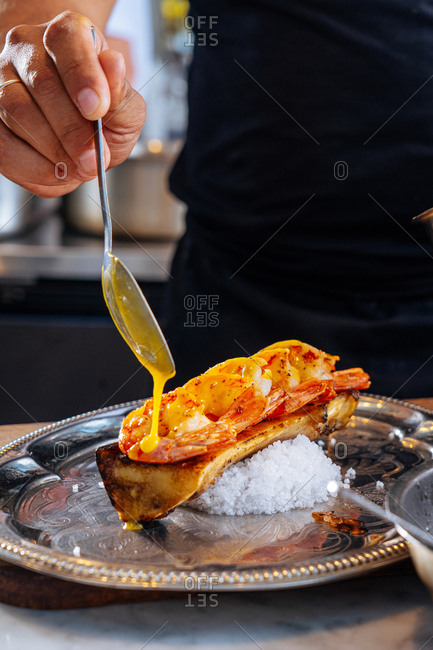 Chef pouring sauce over a shrimp dish