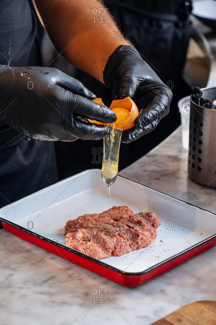 Chef preparing meat for meatballs with egg
