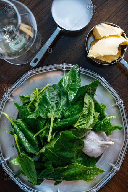 Raw spinach leaves and garlic on silver platter