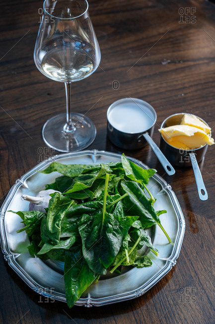 Raw spinach leaves and garlic on silver platter by wine glass