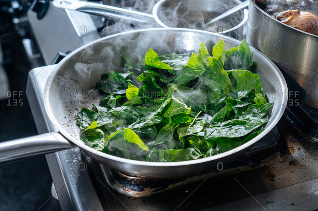 Spinach leaves cooking in a pan
