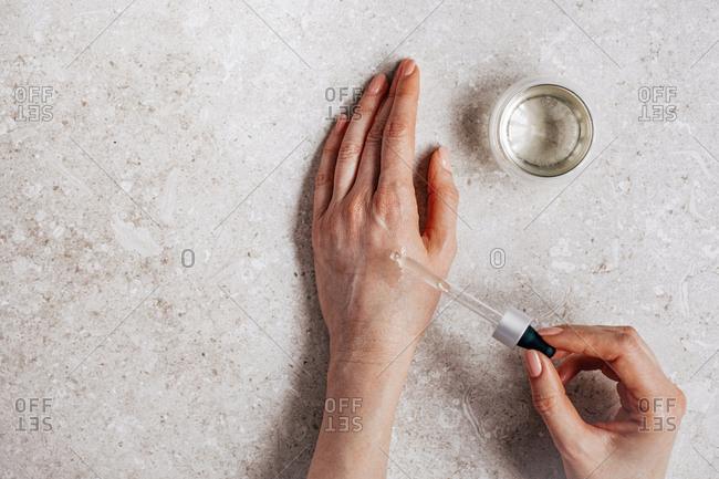 Hands of unrecognisable woman testing cosmetic serum on her skin and holding pipette.