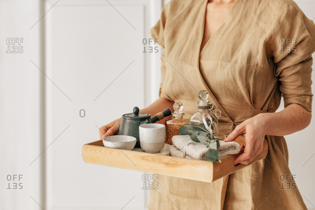 Hands of unrecognisable woman aromatherapist holding a tray with tea and spa objects.