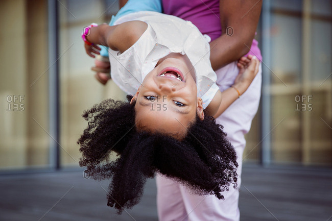 Portrait of smiling young girl with afro hair being held upside down