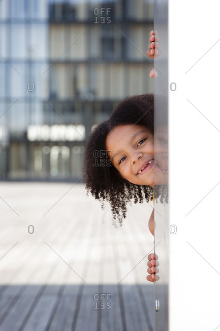 Smiling young girl with afro hair peeking behind wall
