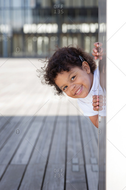 Smiling preschooler with afro hair peeking behind wall