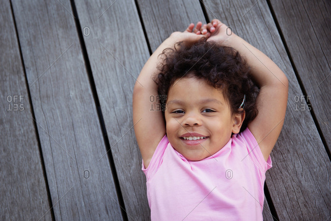 Portrait of smiling child with curly hair lying on wooden deck