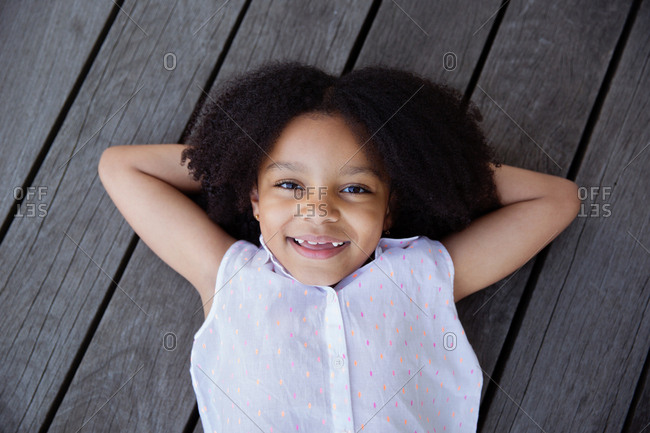 Portrait of smiling young girl with afro hair lying on wooden deck