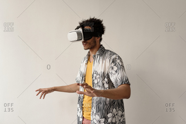 Young male student playing games using virtual reality headset