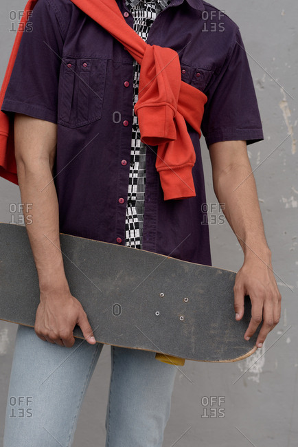 Unrecognizable young man wearing casual outfit holding skateboard