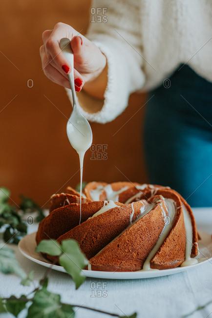 Baker drizzling icing over bundt cake