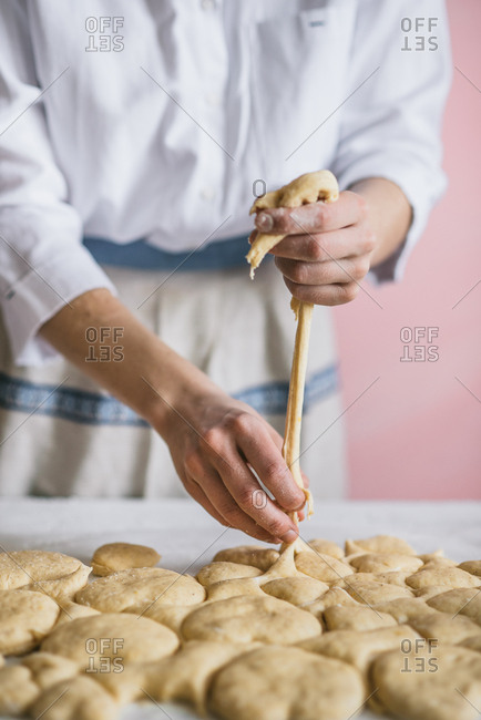 Woman working with heart shaped dough for donuts