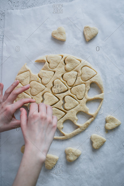 Woman cutting heart shapes into dough for donuts