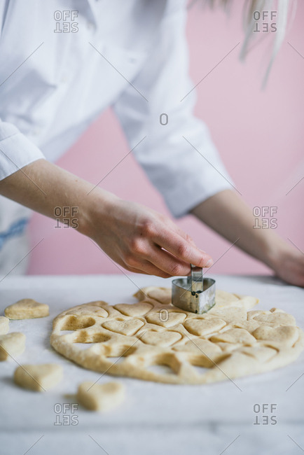 Baker cutting heart shapes into dough for donuts
