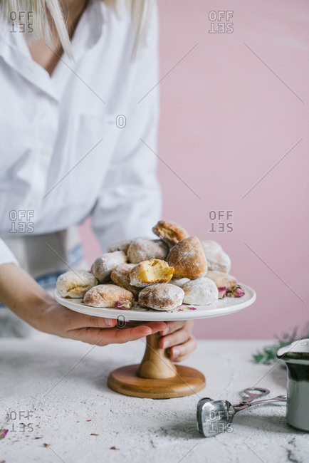 Baker holding stand filled with heart shaped donuts