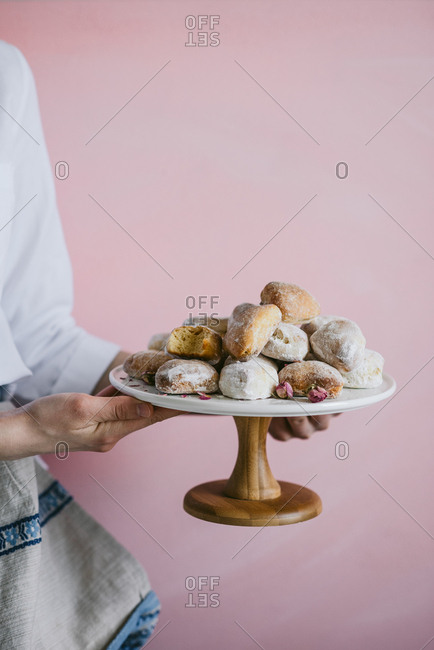 Woman holding stand filled with heart shaped donuts