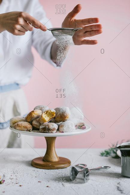 Baker sifting powdered sugar onto heart shaped donuts