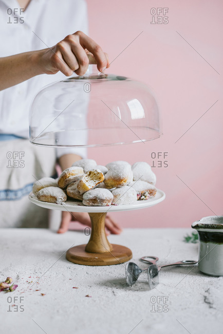 Woman placing lid over stand with heart shaped donuts