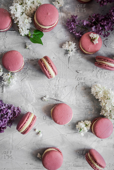 Pink macarons on light background with lilacs