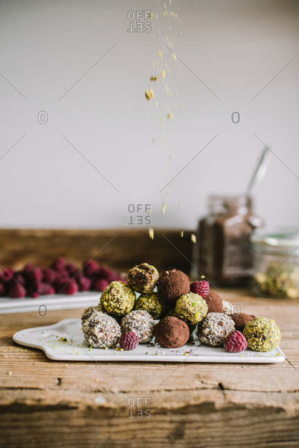 Variety of fresh baked truffles and raspberries being topped with pistachios